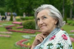 Senior woman on walk in summer park Stock Image