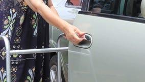 Senior woman with walker open car door. Senior woman with walker open car door at home stock footage