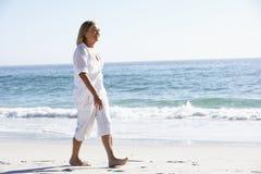 Senior Woman Walking along Sandy Beach Stock Photo