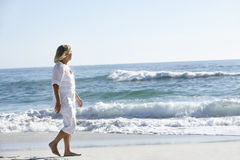 Senior Woman Walking along Sandy Beach Stock Images