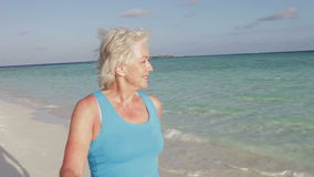 Senior Woman Walking On Beautiful Beach stock footage