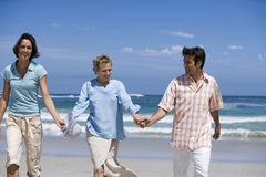 Senior woman walking with couple on beach, holding hands, smiling, front view Stock Images