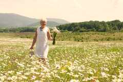 Senior woman walking on the flower field Royalty Free Stock Images