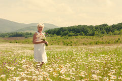 Senior woman walking on the flower field Stock Photo