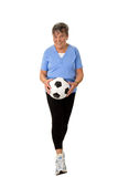 Senior woman walking with football Stock Photography