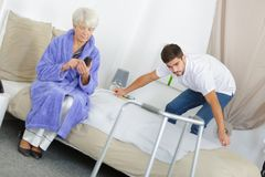 Senior woman with walking frame while caretaker making bed. Senior women with walking frame while caretaker making her bed Stock Photography