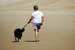 Senior woman walking her dog Stock Images