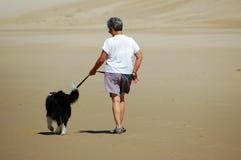 Senior woman walking her dog Stock Images