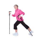 Senior Woman Walking With Hiking Poles Stock Image