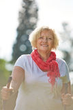 Senior woman walking with hiking sticks in summer Royalty Free Stock Photo