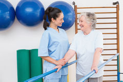 Senior woman walking with parallel bars with therapist Royalty Free Stock Photos