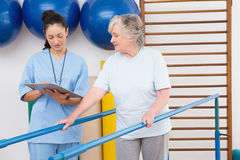 Senior woman walking with parallel bars with therapist Royalty Free Stock Photo