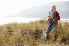 Senior Woman Walking Through Sand Dunes On Winter Beach Stock Images