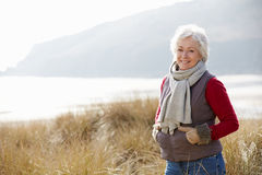 Senior Woman Walking Through Sand Dunes On Winter Beach Stock Photography