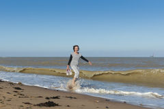 Senior woman walking in the sea. Mature woman walking in the sea bare feet holding her shoes, caught by a wave and laughing Stock Image