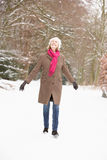 Senior Woman Walking Through Snowy Woodland Royalty Free Stock Photos