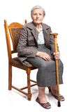 Senior woman with walking stick sitting on chair Royalty Free Stock Images