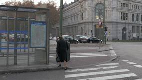 Senior woman walking to bus stop at Plaza de Cibeles in Madrid, Spain stock footage
