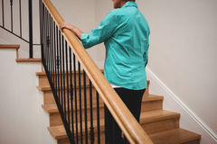 Senior woman walking up stairs. At home Stock Images