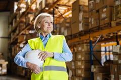Senior woman warehouse manager or supervisor holding white helmet. Stock Photo