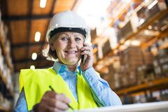 Senior woman warehouse manager or supervisor with smartphone, making phone call. Stock Image