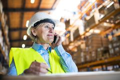 Senior woman warehouse manager or supervisor with smartphone, making phone call. Stock Images