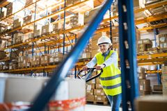 A senior woman warehouse worker pulling a pallet truck with boxes. Royalty Free Stock Photo