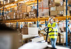 A senior woman warehouse worker pulling a pallet truck with boxes. Royalty Free Stock Images
