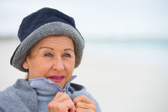 Senior woman in warm jumper in cold weather. Portrait attractive senior woman at beach, feeling cold and frosty, wearing jumper and hat to keep warm outside Stock Image