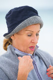 Senior woman in warm jumper in cold weather. Portrait attractive mature woman feeling cold and frosty, wearing jumper and hat to keep warm outside, blurred Royalty Free Stock Photo
