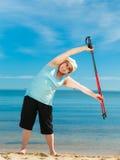 Senior woman warming up with walking poles Stock Image