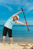 Senior woman warming up with walking poles Stock Photo