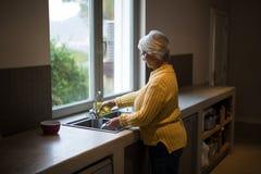 Senior woman washing dish in kitchen sink. At home royalty free stock photo