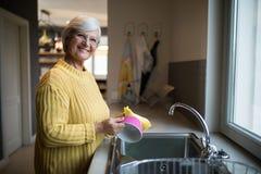 Senior woman washing dish in kitchen sink. Portrait of smiling senior woman washing dish in kitchen sink royalty free stock photo