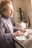 Senior Woman Washing Up At Sink Stock Image