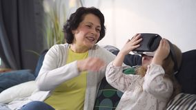 Senior woman watching like her little granddaughter is playing using new futuristic technology. Of 3d augmented virtual reality simulation. Online activity in stock video footage