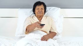Senior woman watching scared movie with tv remote control on bed stock video footage