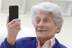 Senior woman watching something to her mobile phone. Happy elderly woman selfie herself with her smart phone Royalty Free Stock Images