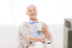 Senior woman watching tv and drinking tea at home. Technology, television, age and people concept - happy senior woman watching tv, drinking tea and changing Royalty Free Stock Images