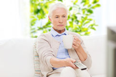 Senior woman watching tv and drinking tea at home. Television, age and people concept - senior woman watching tv, drinking tea and changing channels by remote Stock Images