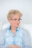 Senior woman watching tv on her sofa Stock Image