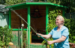 A senior woman with water in the garden Stock Photos