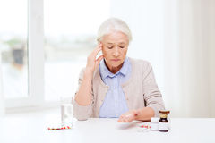 Senior woman with water and medicine at home Royalty Free Stock Images