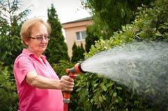 Senior woman watering garden Stock Photo