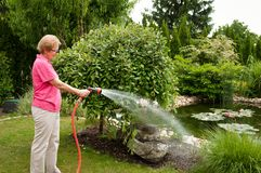 Senior woman watering garden Royalty Free Stock Photos