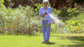 Senior woman watering lawn by hose at garden stock video footage