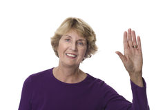 Senior woman waving hand in greeting. Smiling senior woman waving her hand to say goodbye or to greet a visitor. Isolated on white Royalty Free Stock Photography