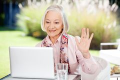 Senior Woman Waving While Video Chatting On Laptop Royalty Free Stock Images