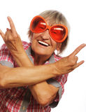 Senior woman wearing big sunglasses doing funky action Royalty Free Stock Photo