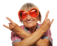 Senior woman wearing big sunglasses doing funky action Royalty Free Stock Photos
